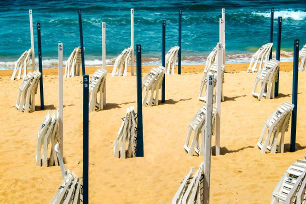 strand am mittelmeer mit gefalteten stühle und sonnenschirme - gratis solarium stock-fotos und bilder