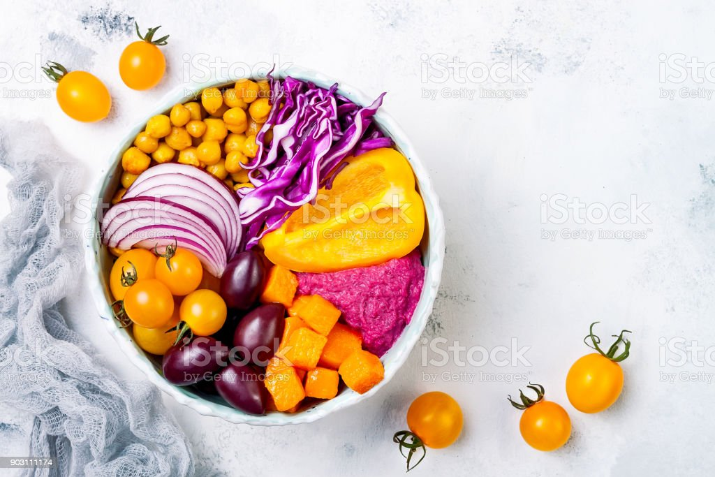 Mediterranean Buddha bowl with roasted pumpkin, olives, turmeric chickpeas, beet hummus, shredded red cabbage, yellow cherry tomatoes. Winter veggies detox bowl stock photo