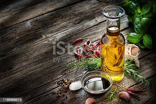 Mediterranean cooking ingredients: olive oil, balsamic vinegar, salt, pepper, rosemary, basil and garlic grouped at the right of a rustic wooden table leaving useful copy space for text and/or logo at the left. Low key DSRL studio photo taken with Canon EOS 5D Mk II and Canon EF 100mm f/2.8L Macro IS USM.