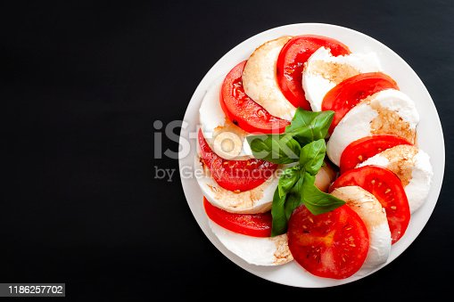Mediterranean cuisine, fresh vegetarian food and italian culinary art concept with Caprese salad made of mozzarella cheese, tomatoes and basil leafs isolated on black background with copy space