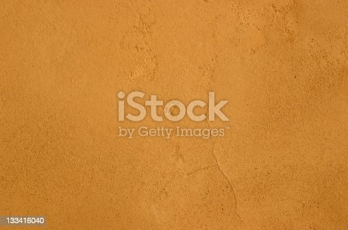 Typicall Mediterranean clay plaster surface, adobe sandy texture with tiny hair cracks.