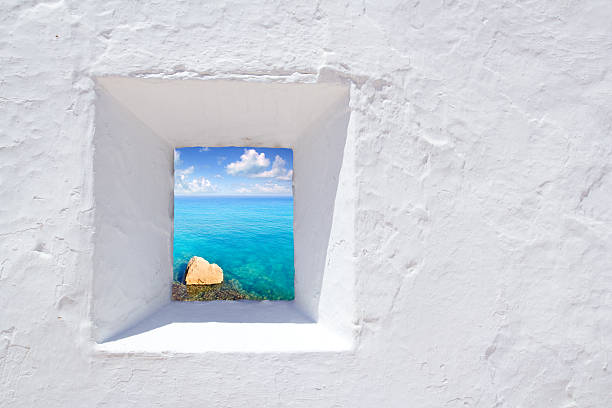 Mediterranean Ibiza seascape through window in white wall Ibiza mediterranean white wall window with Formentera beach view mediterranean sea stock pictures, royalty-free photos & images