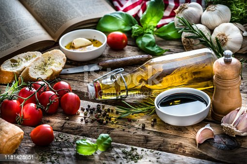 Mediterranean ingredients shot on rustic wooden table. Ingredients and spices included in the composition are olive oil, balsamic vinegar, garlic, parsley, tomatoes, peppercorns, rosemary, basil and bread. XXXL 42Mp studio photo taken with SONY A7rII and Zeiss Batis 40mm F2.0 CF