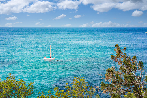 Mediterranean landscape of Ibiza island i Spain. Mediterranean sea with a sailing boat in summer. Suitable as an example of luxury yacht tourism in the Mediterranean in contrast to the humanitarian crisis of migrants at sea or the tourism crisis caused by the pandemic.