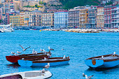 Mediterranean landscape. Sea view of the Gulf of Naples. Seagulls sit on boats moored in the bay. Cityscape of Naples, view of Mergellina district. The province of Campania. Italy.