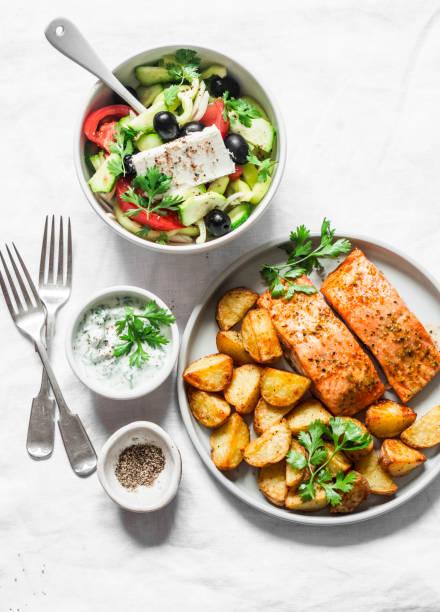 Mediterraner Mittagstisch - gebackener Zitronenlachs mit Kartoffeln, griechischer Salat, Tzadziki-Sauce auf leichtem Hintergrund, Ansicht von oben. Flache Verlegung – Foto