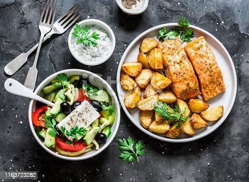 Mediterranean lunch table - baked lemon salmon with potatoes, greek salad, tzadziki sauce on dark background, top view. Flat lay
