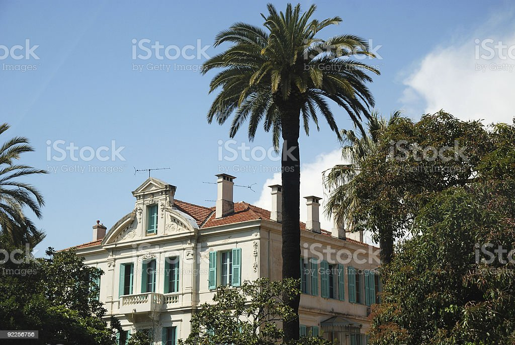 Mediterranean mansion in green trees and palms royalty-free stock photo