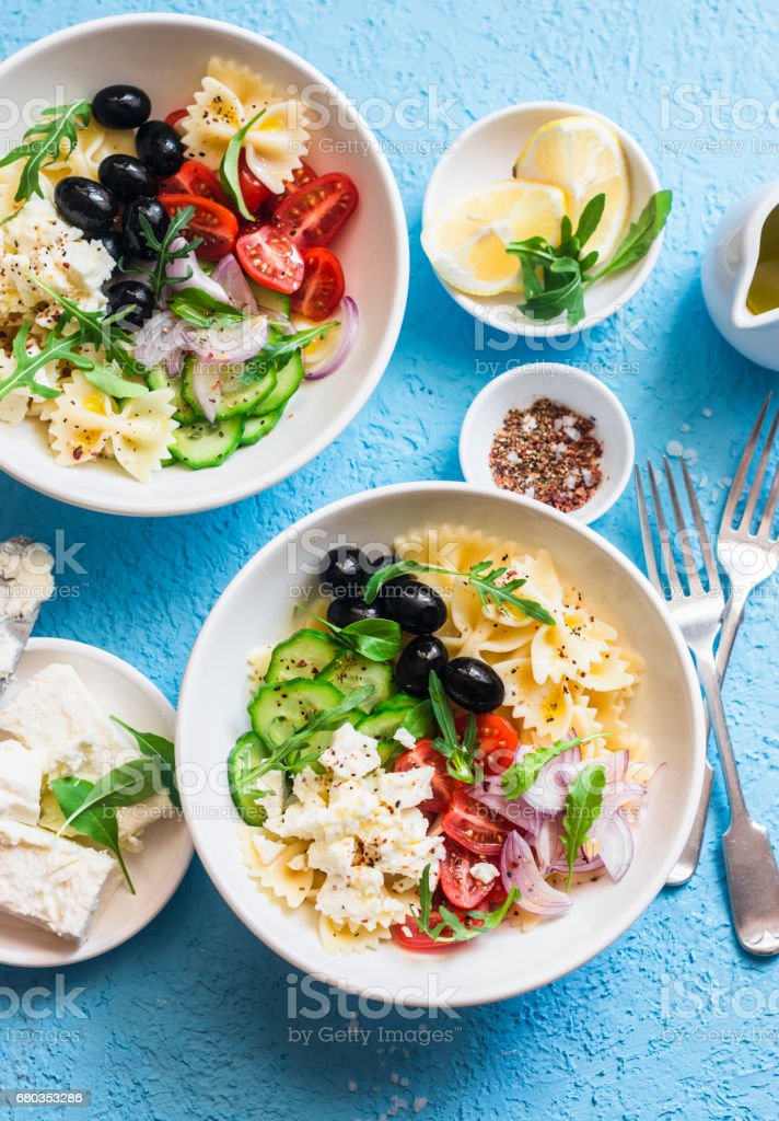 Mediterranean pasta salad. Pasta  farfalle, tomatoes, cucumbers, olives, feta cheese and arugula salad. On a blue background, top view. Flat lay royalty-free stock photo