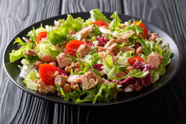 Mediterranean salad with tuna fish, borlotti beans, cherry tomatoes, lettuce close-up. horizontal stock photo