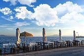 Mediterranean sea scenery, greek tavern tables and umbrellas
