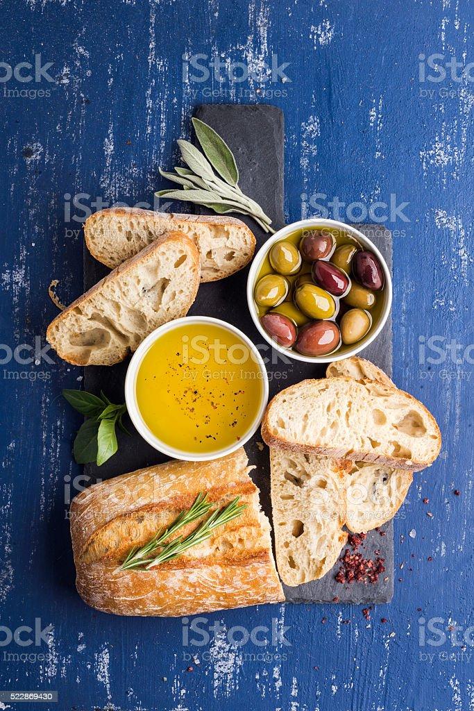 Mediterranean snacks set. Olives, oil, herbs and sliced ciabatta bread stock photo