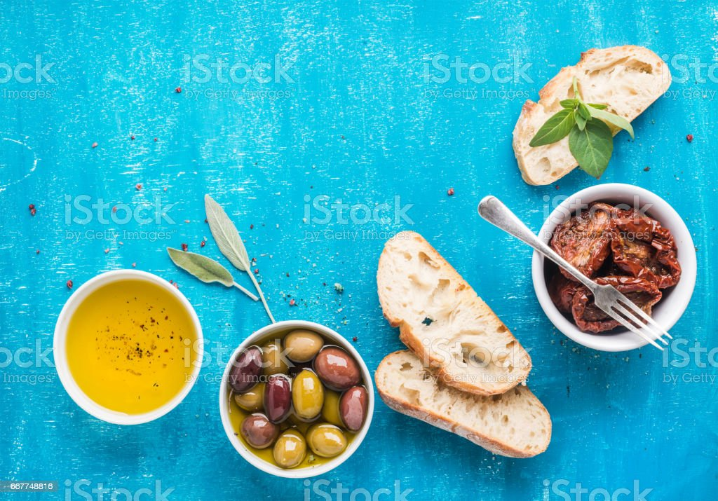 Mediterranean snacks set. Olives, oil, sun-dried tomatoes, herbs and sliced ciabatta bread on over blue painted background stock photo