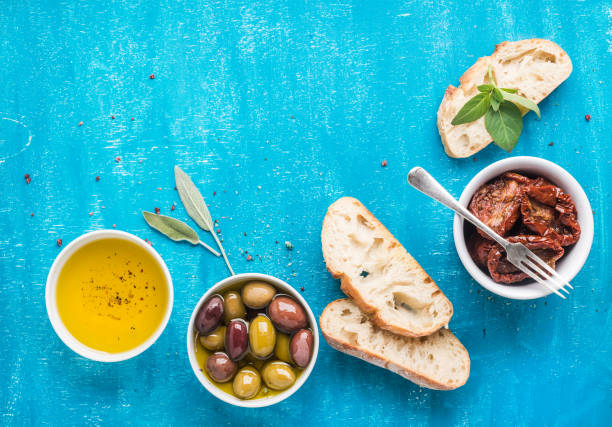 mediterranean snacks set. olives, oil, sun-dried tomatoes, herbs and sliced ciabatta bread on over blue painted background - mediterranean food imagens e fotografias de stock