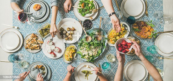 Mediterranean style dinner. Flat-lay of table with salad, starters, pastries over blue table cloth with hands holding drinks, sharing food, top view, wide composition. Holiday vegetarian party concept