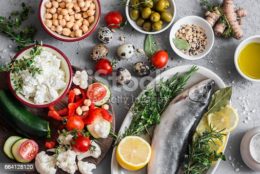 istock Mediterranean style food background. Fish, vegetables, herbs, chickpeas, olives, cheese on grey background, top view. Healthy food concept. Flat lay 664128120
