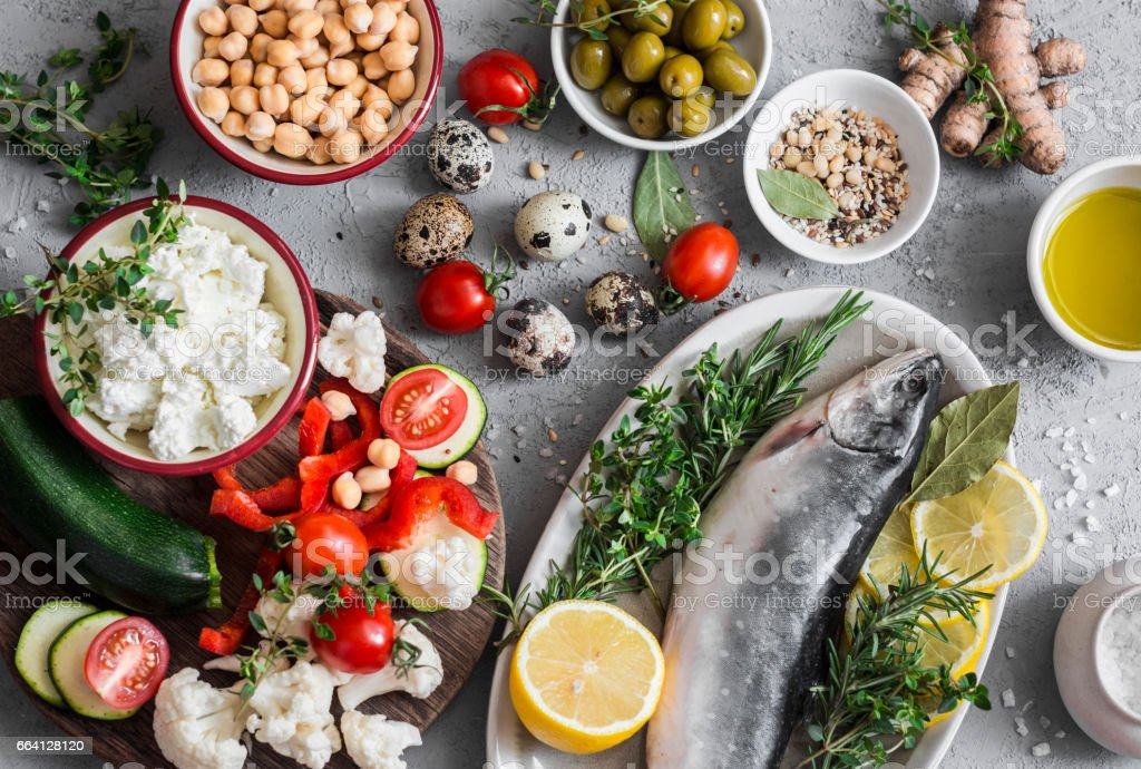 Mediterranean style food background. Fish, vegetables, herbs, chickpeas, olives, cheese on grey background, top view. Healthy food concept. Flat lay stock photo