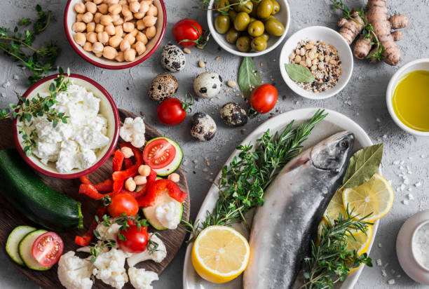 mediterranean style food background. fish, vegetables, herbs, chickpeas, olives, cheese on grey background, top view. healthy food concept. flat lay - mediterranean food imagens e fotografias de stock