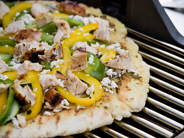 Mediterranean style gourmet barbequed pizza on a grill stock photo
