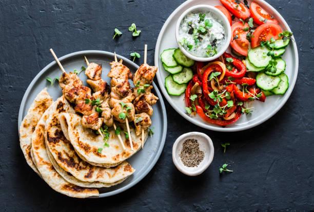 Mittagstisch im mediterranen Stil-Truthahn, Fladenbrot, Tomaten, Gurkensalat, gebackener süßer Pfeffer, Joghurtkrautsoße auf dunklem Hintergrund, Top-Aussicht – Foto