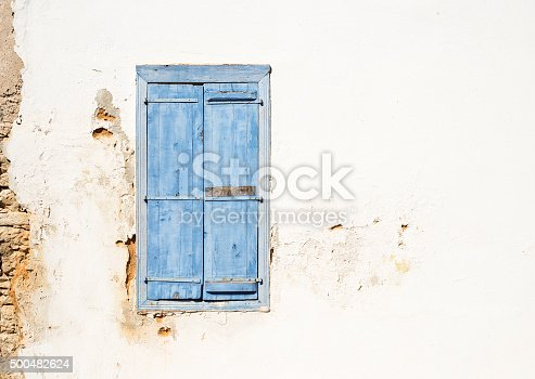 Mediterranean style window. Blue on yellow wall with closed shutters
