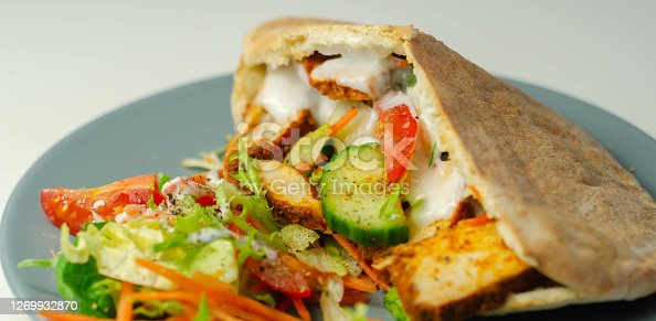 Mediterranean style pitta prepared with spicy chicken, cucumber, tomato, salad and mayo sauce, tasty food