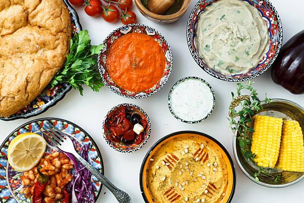 Mediterranean traditional meze: hummus, babaganoush, harissa, tzatziki on white background stock photo