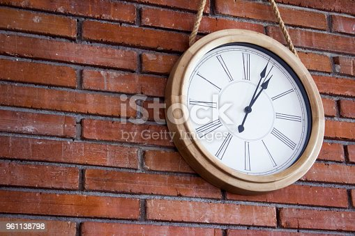 671883446istockphoto Medium close shot of a wooden wall clock with roman numerals hanging in a red brick wall. 961138798