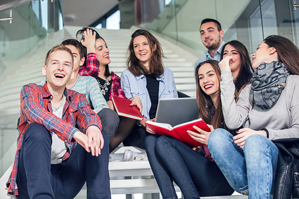 Medium group of students studying on steps of school building Medium group of students studying on steps of school building high school building stock pictures, royalty-free photos & images
