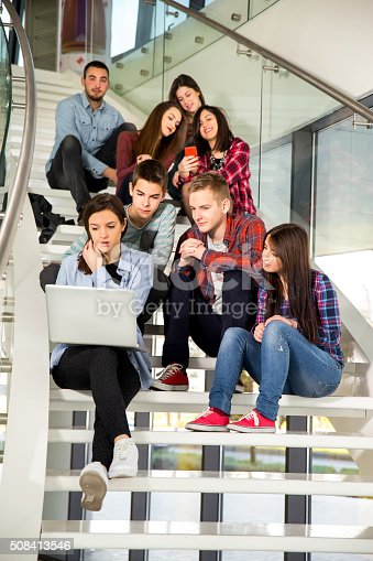 istock Medium group of students studying on steps of school building 508413546