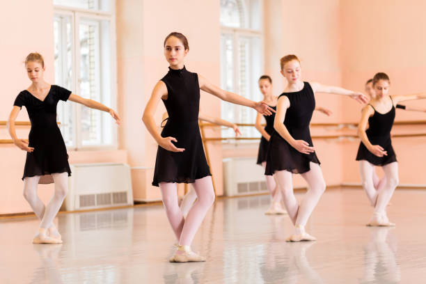 Medium group of teenage girls practicing ballet moves Medium group of teenage girls in black dresses practicing ballet moves in large dancing studio. dance studio stock pictures, royalty-free photos & images
