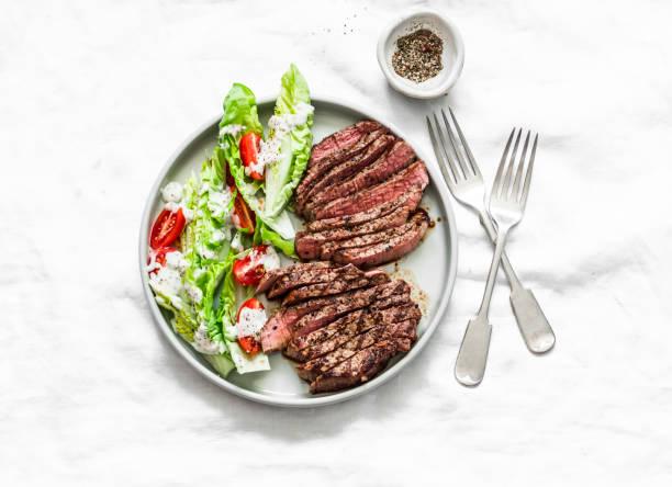 Mittlere seltene Rindfleisch Steak und romaine Kirschtomaten Joghurt Dressing Salat auf einem hellen Hintergrund, Top-Ansicht. Köstliches ausgewogenes Essen – Foto