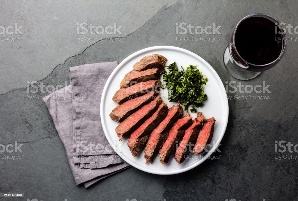 Medio raro bistec servido en plato blanco con vino tinto - Foto de stock de Alimento libre de derechos