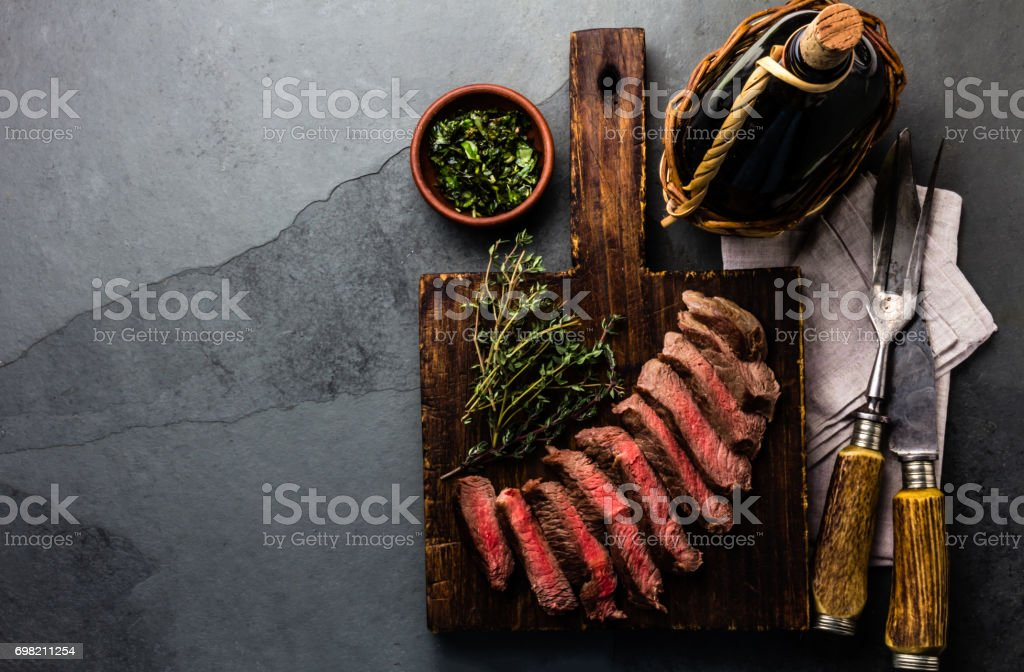 Medium rare beef steak with wine on slate background stock photo