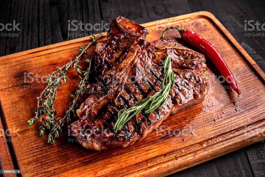 Medium rare grilled steak on rustic cutting board with rosemary and spices , dark rustic wooden background, top view royalty-free stock photo