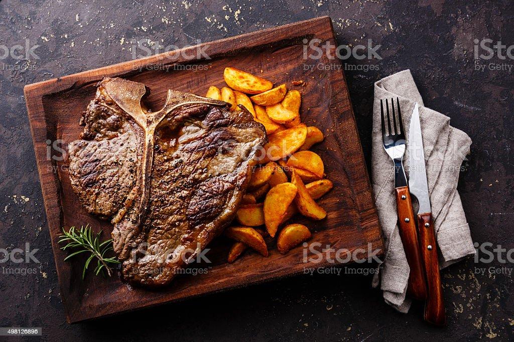Medium rare Grilled T-Bone Steak with potato wedges stock photo