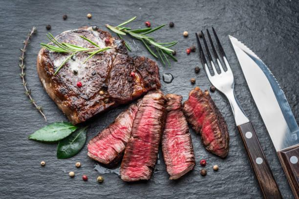 Medium rare Ribeye steak with herbs on graphite board. stock photo