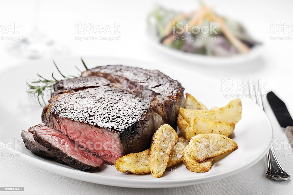 Medium rare ribeye steak with side of seasoned potato fries stock photo