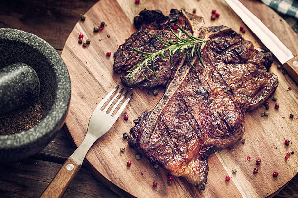 Medium Roasted T-Bone Steak Delicious T-Bone Steak Medium Roasted with Herbs and Pepper. The steak is on a wooden plate served with knife and fork. red meat stock pictures, royalty-free photos & images