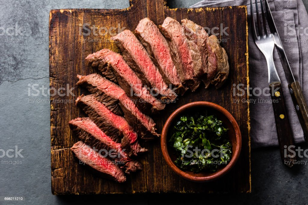 Mediun rare beef steak on wooden board. Top view stock photo