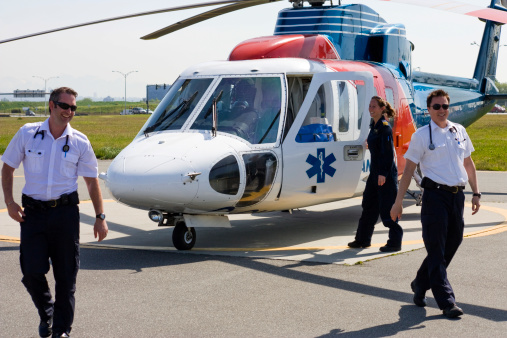 A female pilot and two male paramedics sharing a laugh after a medivac flight.