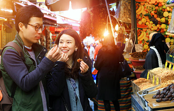 Medjool Dates Taste Sweet Korean couple Eating delicious medjool dates eat bazaar Istanbul. korean ethnicity stock pictures, royalty-free photos & images