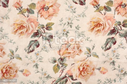 Antique floral fabric with clusters of pink flowers on a beige background..