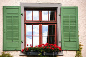 window with green shutters and reflection of sky in the glass, Meersburg, Germany