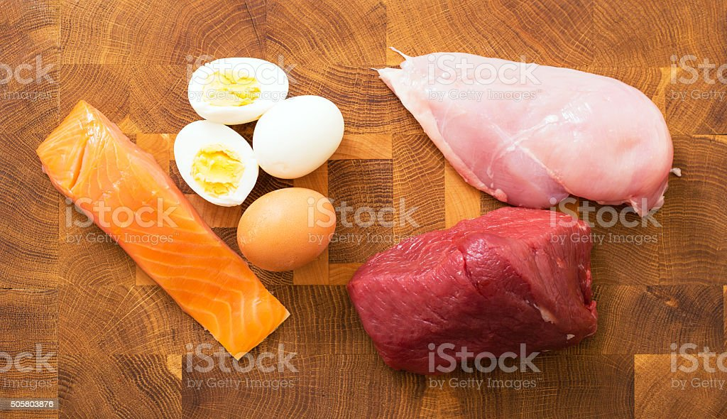 Meet, fish, eggs on kitchen table stock photo