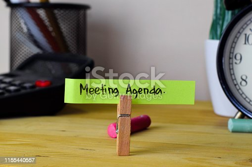 istock Meeting Agenda. Handwriting on sticky notes in clothes pegs on wooden office desk 1155440557