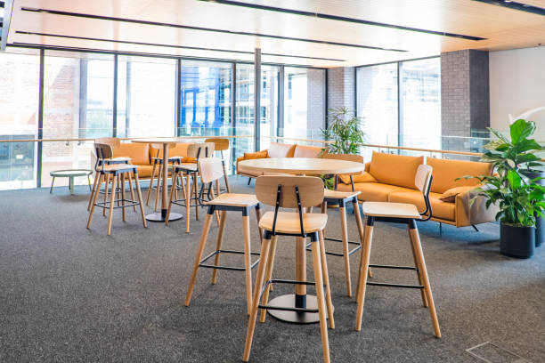 Meeting area in a modern creative coworking office space with couch, sofa, bar stools, leaner tables, carpet. No people, modern building interior. stock photo