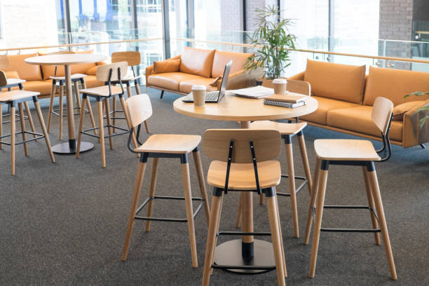 Meeting area in a modern creative coworking office space with laptop computer and takeaway coffee cups on bar leaner table. No people, modern building interior. stock photo