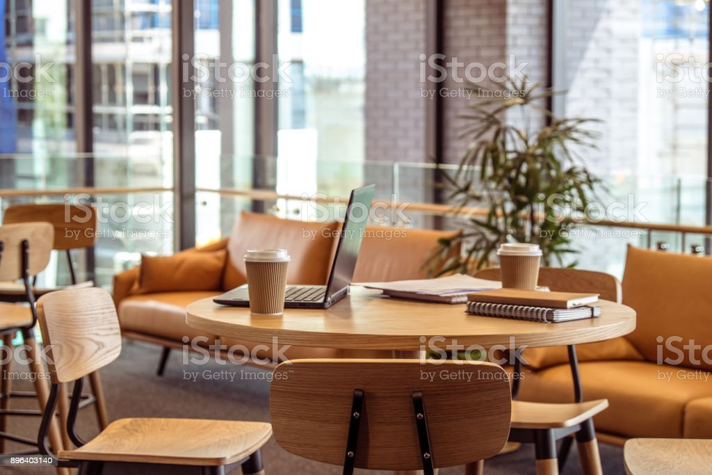 Meeting area in a modern creative coworking space with laptop computer, stationery, papers and takeaway coffee cups on bar leaner table. stock photo