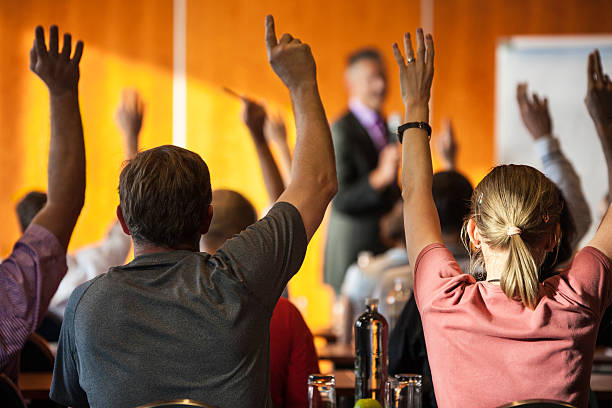 Meeting attendees with raised hands in foreground stock photo